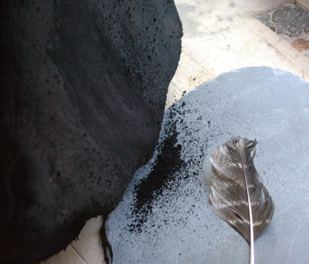 Collecting fir pitch soot (aka  lampblack ) off of a flat rock for use in ink making.