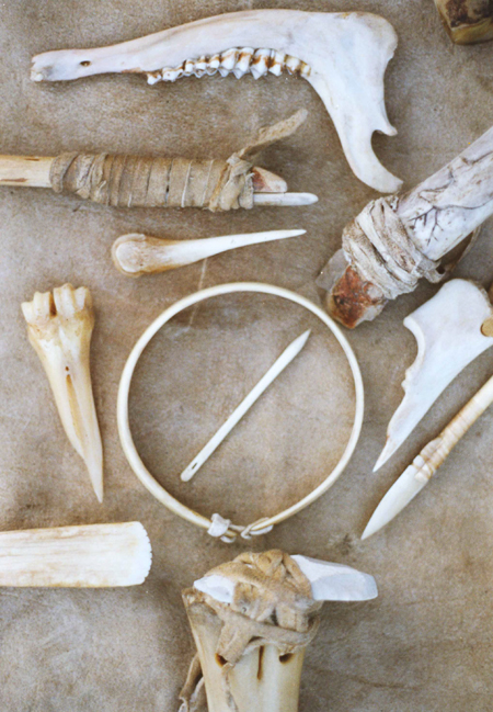 Some bone and anlter objects.  The hoop in the center is elk antler thinned by scraping with stone flakes.  Bottom is a bone handle for a dry hide scraper of chert stone.  top right is a handle for a stone scraper with relief carving.  top left, is an antler pressure flaker bound to a wooden handle.  All of these items are made with primitive processes.