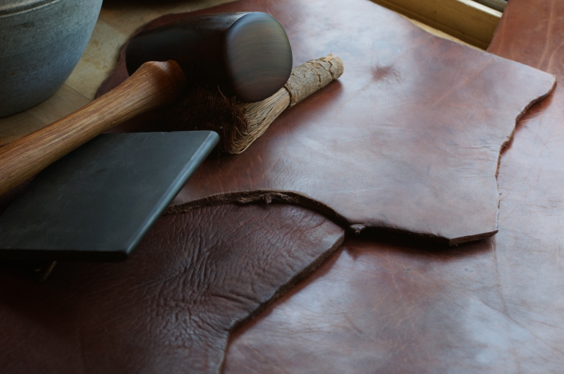 Pounded leather with stone sleeker and ironwood mallet.  The bit on the lower left is the same as the upper piece, but unpounded.