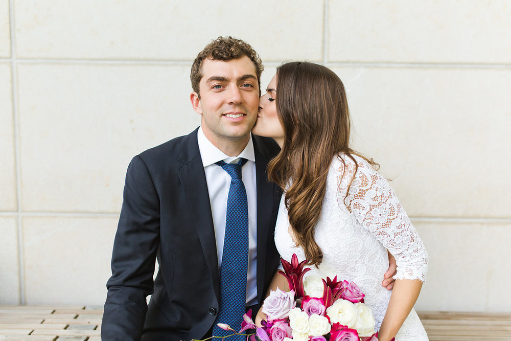 Seattle Courthouse Wedding | Seattle Municipal Court | Downtown Seattle Wedding | Intimate Elopement Wedding | Beautiful Simple Courthouse Wedding | Bride and Groom Portrait | White Wedding Jumpsuit Outfit | Beautiful Purple Wedding Bouquet | Mastin Labs Fuji 400 | Bride Kissing Groom on Cheek
