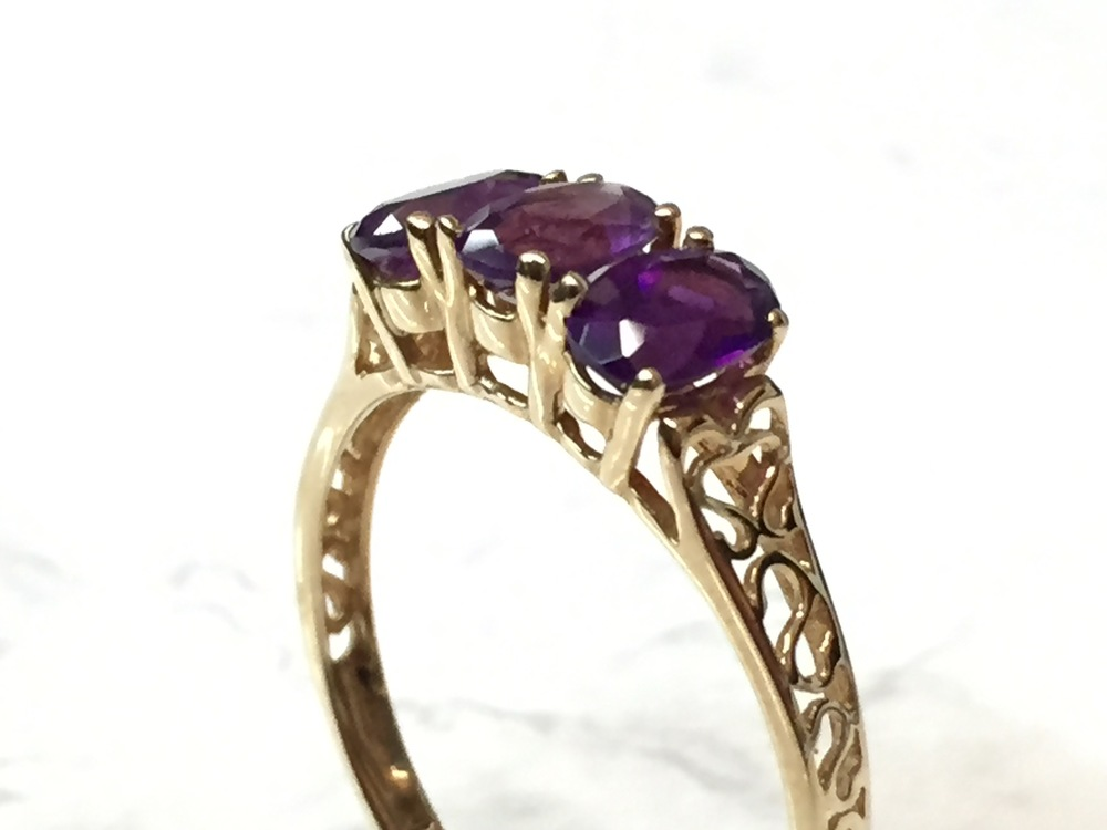 Three-stone amethyst ring in 10K yellow gold with decorative filigree, on sale for $150.00