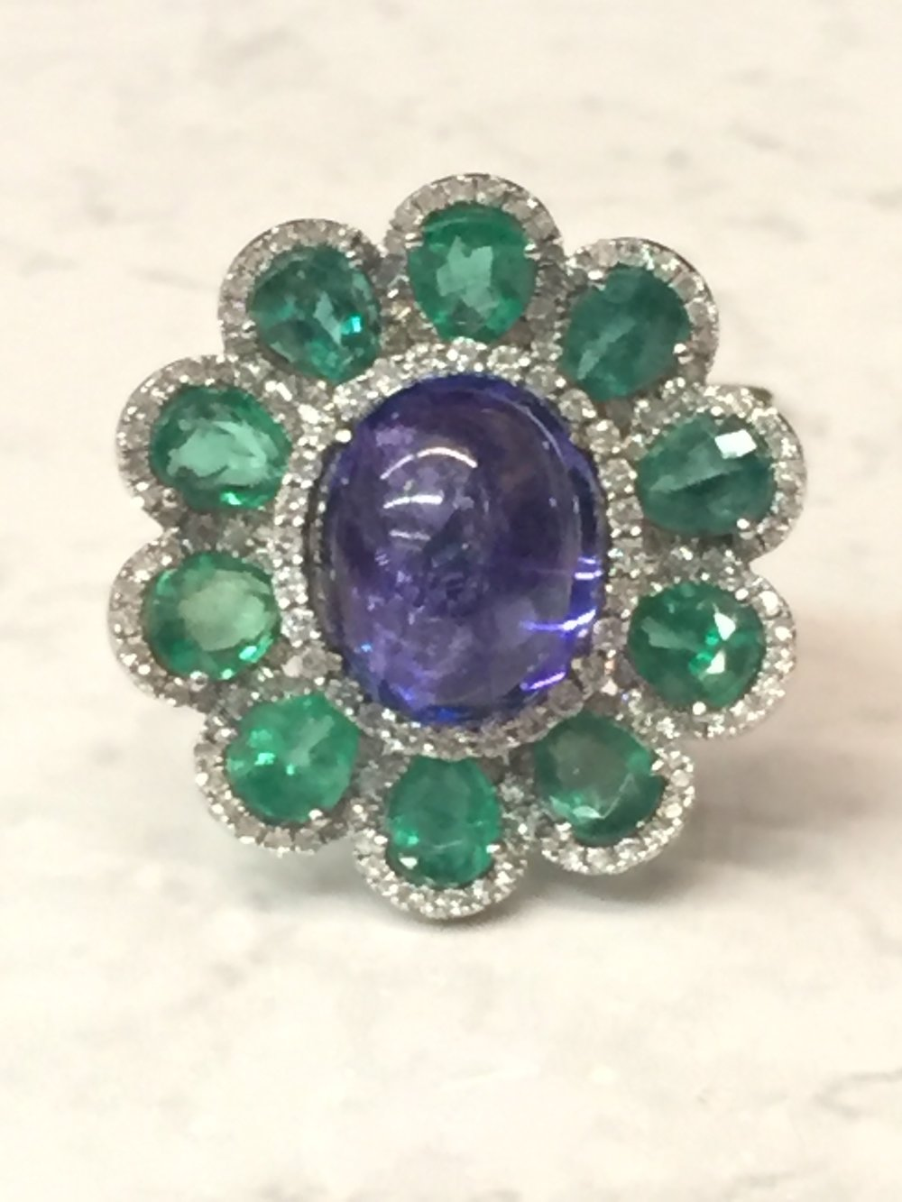 Unique tanzanite (6.97 ct) emerald (3.44 ctw) and diamond (0.74 ctw) ring in 18K white gold.  $8,500.00