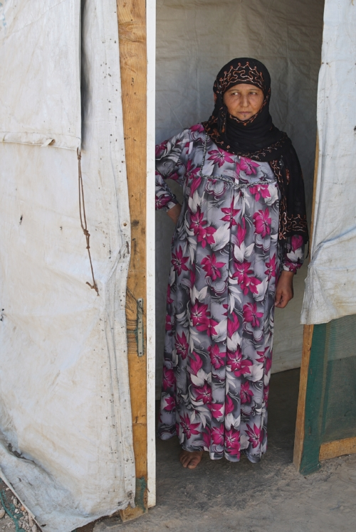 Host family mother in the doorway of their tented home