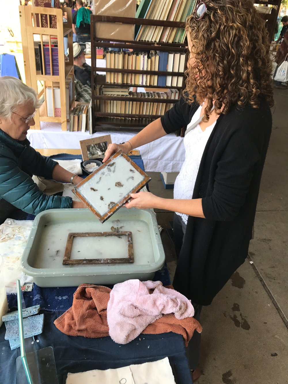 I stopped to look at some beautiful handmade paper and ended up making some myself. Here I am dipping a screen into wet pulp marked with paper wasp's at Karen Koykka O'Neal's Out of Hand Papermaking booth.