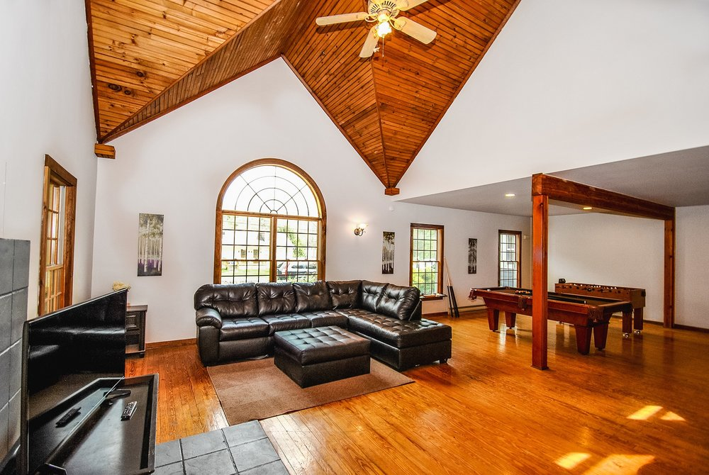 Pennsylvania Mountains, PA - Airbnb / VRBO - Cabin and House Rental with Indoor Swimming Pools in the Poconos: Le Chateau Magnifique    Sleeps 21: 8 Bedrooms (8 queen beds), 8.5 Baths, Game Room with Roku w/Sling/Netflix, Gas Firepit on the side, BBQ Grill, Wood Fireplace in Living Area and a Seperate Gas Fireplace in Great Room, Pool Table, Foosball Table and huge dining room table seats 12-14.