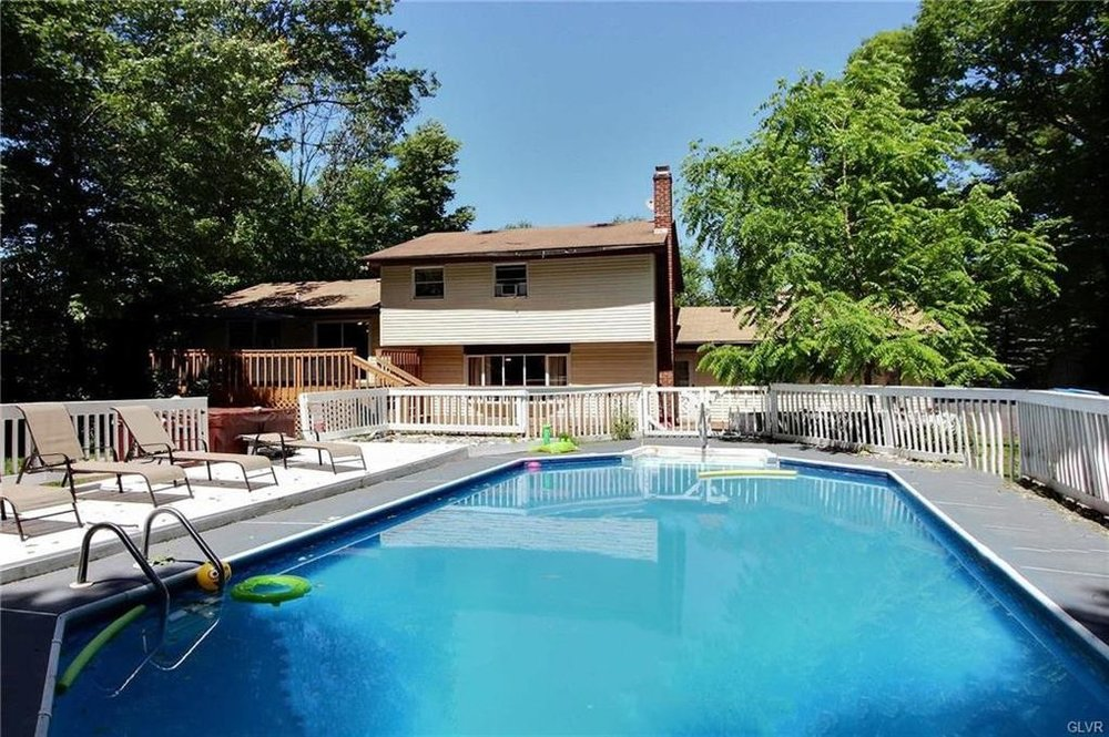 Pennsylvania Mountains, PA - Airbnb / VRBO - Cabin and House Rental with Indoor Swimming Pools in the Poconos: Water by a Cellar Door    Sleeps 14-16: 6 Bedrooms (6 queen beds), 3 Baths, Beautiful Large Private Pool (Only Open Early May - Late Oct), Game Room with Roku w/Sling/Netflix, Firepit in the Back, BBQ Grill, Poker Table and a Hot Tub next to the pool.