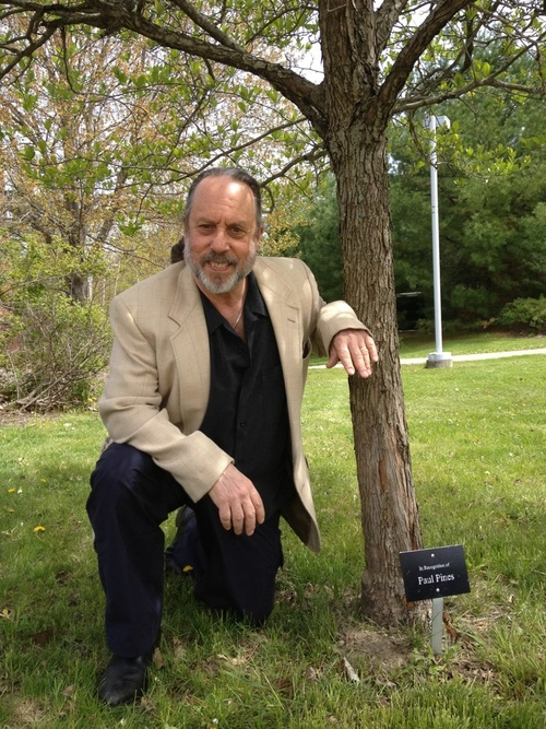 PAUL PINES WITH THE TREE PLANTED IN RECOGNITION OF HIS WORK AS A PROFESSOR AT SUNY ADIRONDACK.