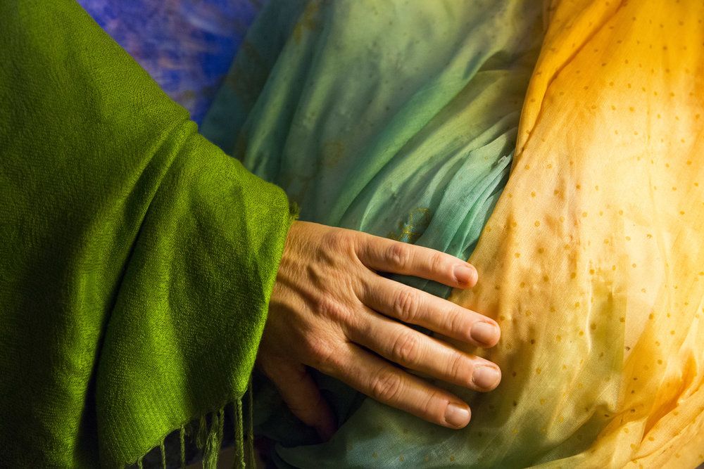 Lorian Moore touches a plaster mold, covered in a colorful scarf, of her pregnant belly from her first child, Sage.