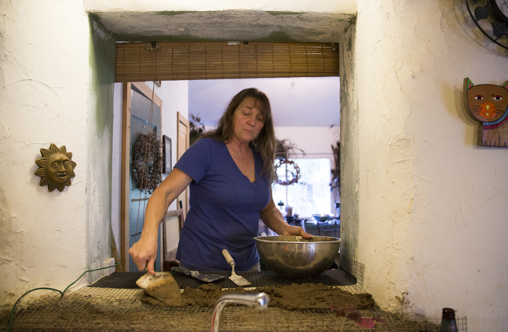 "Normal   0           false   false   false     EN-US   JA   X-NONE                                                                                                                                                                                                                                                                                                                                                                              /* Style Definitions */ table.MsoNormalTable 	{mso-style-name:""Table Normal""; 	mso-tstyle-rowband-size:0; 	mso-tstyle-colband-size:0; 	mso-style-noshow:yes; 	mso-style-priority:99; 	mso-style-parent:""""; 	mso-padding-alt:0in 5.4pt 0in 5.4pt; 	mso-para-margin:0in; 	mso-para-margin-bottom:.0001pt; 	mso-pagination:widow-orphan; 	font-size:12.0pt; 	font-family:Cambria; 	mso-ascii-font-family:Cambria; 	mso-ascii-theme-font:minor-latin; 	mso-hansi-font-family:Cambria; 	mso-hansi-theme-font:minor-latin;}     Lorian Moore smooths out cob clay, a subsoil of water, and other kinds of fibrous organic material on her window behind the kitchen sink. The family lives in a straw-bale house that they constructed on part of their 43 acres of land in 1994 out of recycled materials in the small town of Leasburg, Missouri."