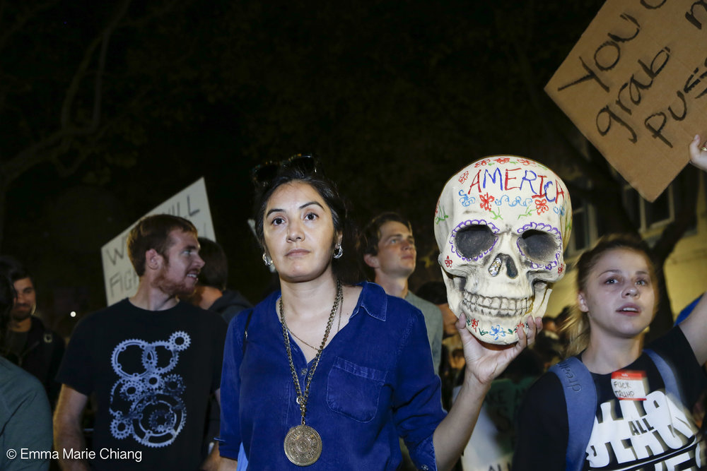 "Aide Rodreguez holds a skull that reads ""American"" while walking with hundreds of anti-Trump protesters through the streets of downtown Oakland Wednesday Nov. 9 2016. Photo by Emma Chiang"