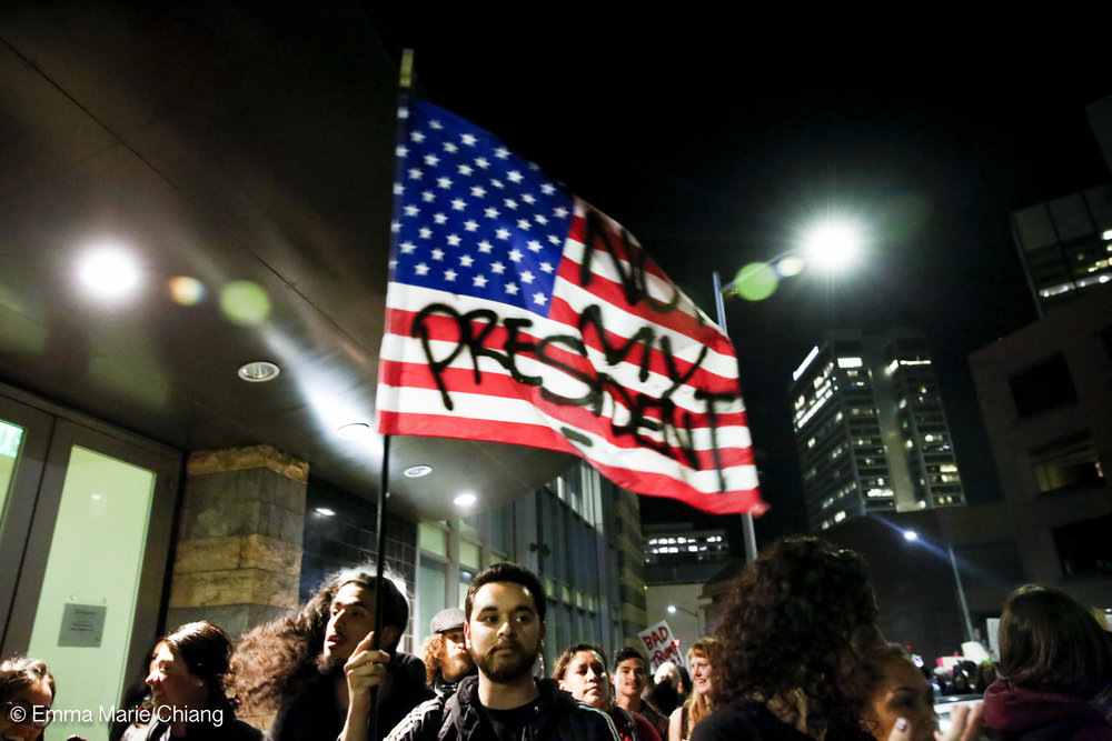 "A protester waves a flag that reads ""Not my America"" during an anti-Trump protest through the streets of downtown Oakland Wednesday Nov. 9 2016. Photo by Emma Chiang"