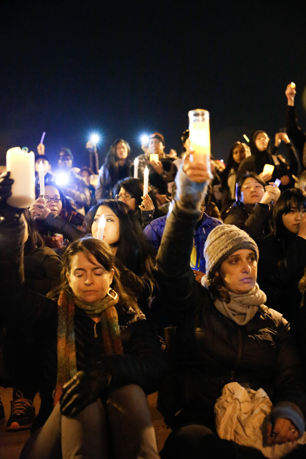 Mourners raise candles during a moment of silence at a vigil at Lake Merritt Pergola on Monday December 5, 2016. in honor of the 36 people who died in the Oakland Fire at the Ghost Ship warehouse party Friday, December 2.