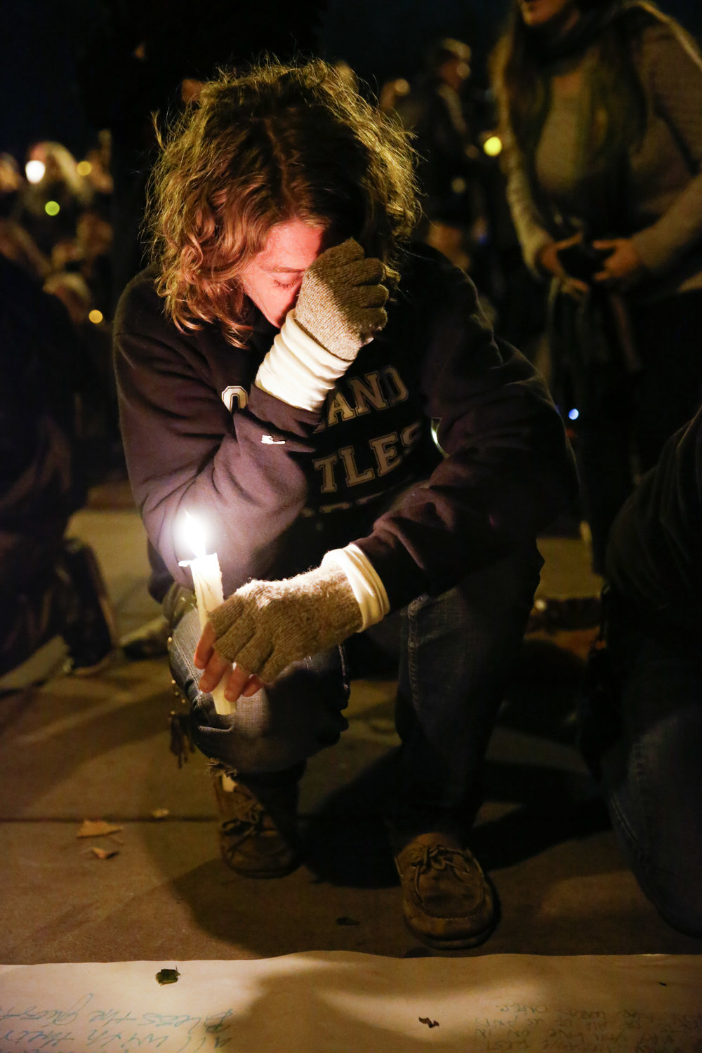 A women holds back tears at a vigil for the victims of the fatal warehouse fire during a vigil at Lake Merritt Pergola in Oakland, California, U.S. December 5, 2016.
