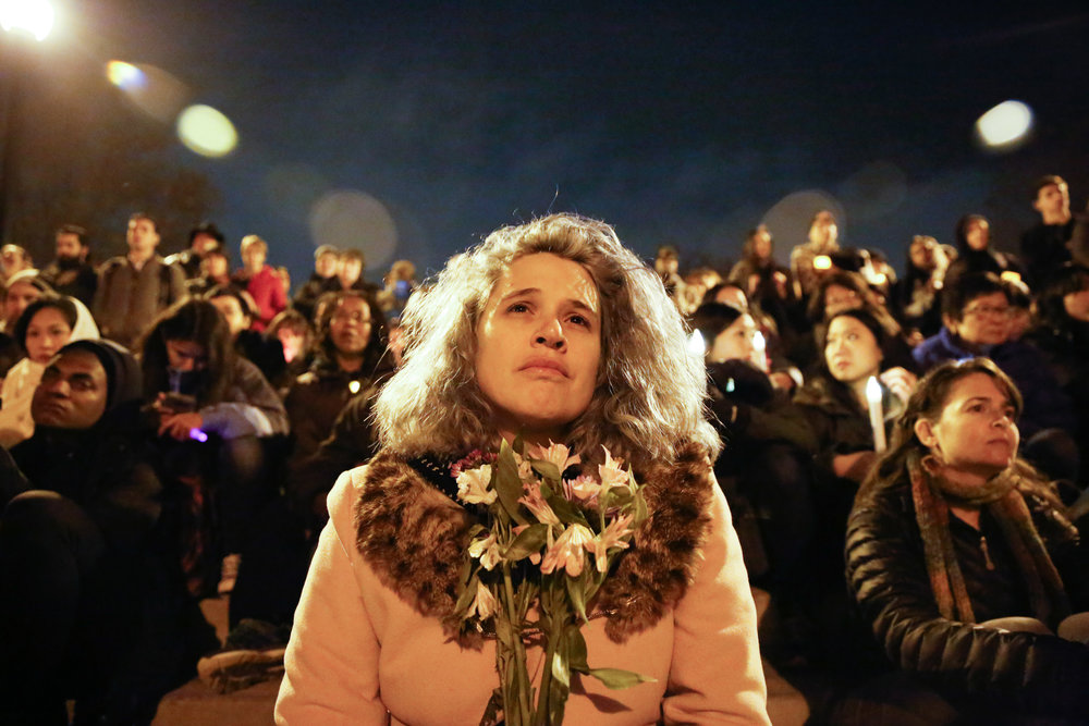 A woman holds flowers in honor of the 36 people who died in the Oakland Fire at the Ghost Ship warehouse party Friday, December 2. held at at Lake Merritt Pergola on Monday December 5, 2016.