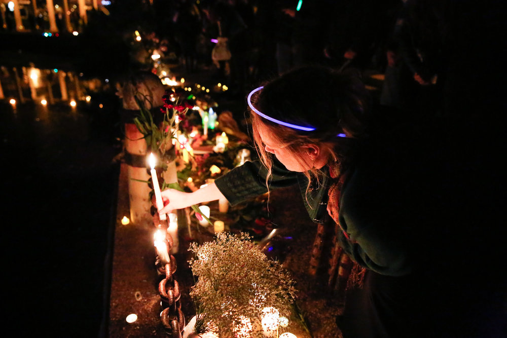 A women places a candle at a memorial site in honor of the 36 people who died in the Oakland Fire at the Ghost Ship warehouse party Friday, December 2.
