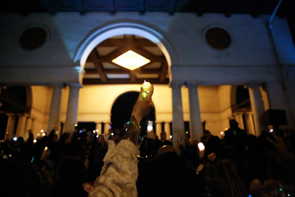 Mourners raise candles during a moment of silence at the vigil at Lake Merritt Pergola on Monday December 5, 2016. in honor of the 36 people who died in the Oakland Fire at the Ghost Ship warehouse party Friday, December 2.
