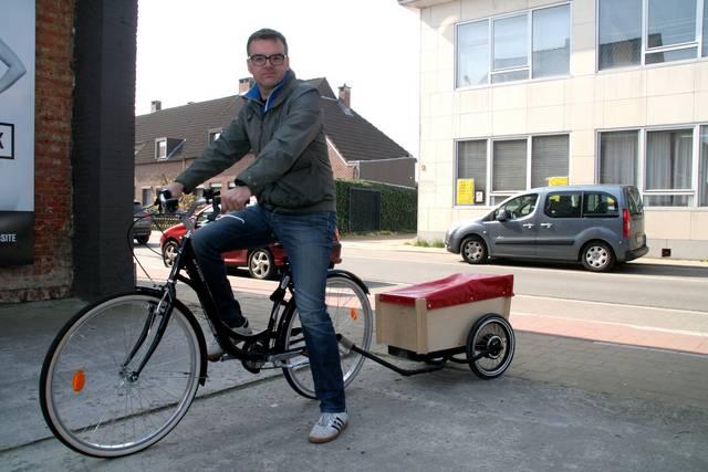 Dirk Verhaeghe met de fietskar 'Urban Nomad'. Het karretje detecteert wanneer de fiets remt en past zijn aandrijving en snelheid aan. - Foto Joris Vergauwen