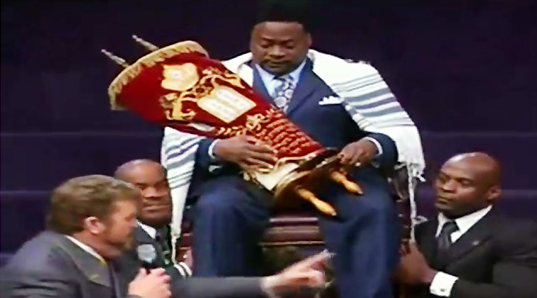 """Bishop"" Eddie Long is hoisted high and lifted up as the crowd screams with ecstasy."