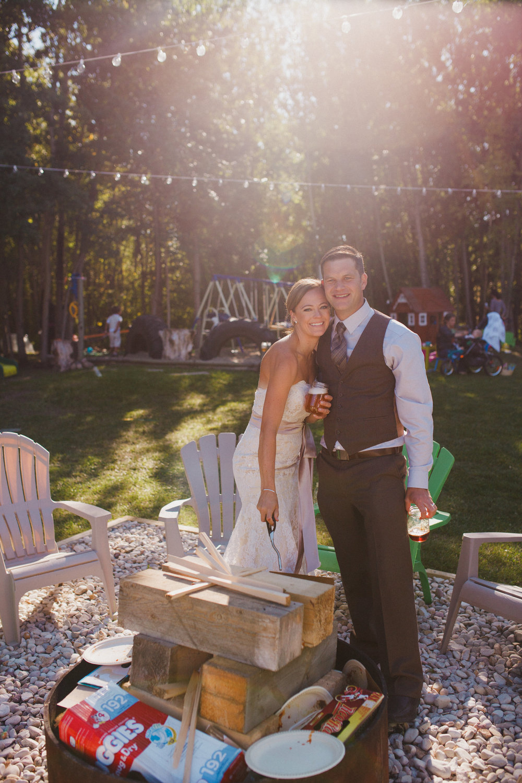 Lighting a bonfire instead of cutting a cake. Family, backyard wedding near Sherwood Park, Alberta.
