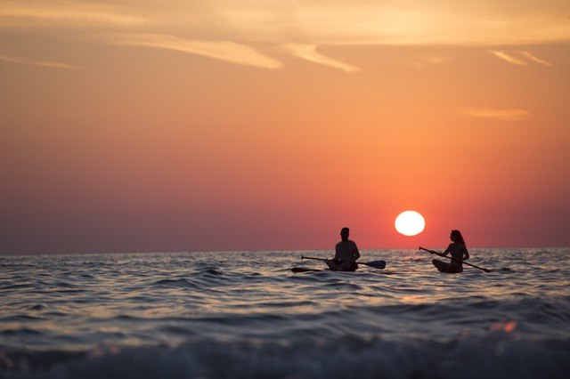 two people kayaking in the ocean at sunset
