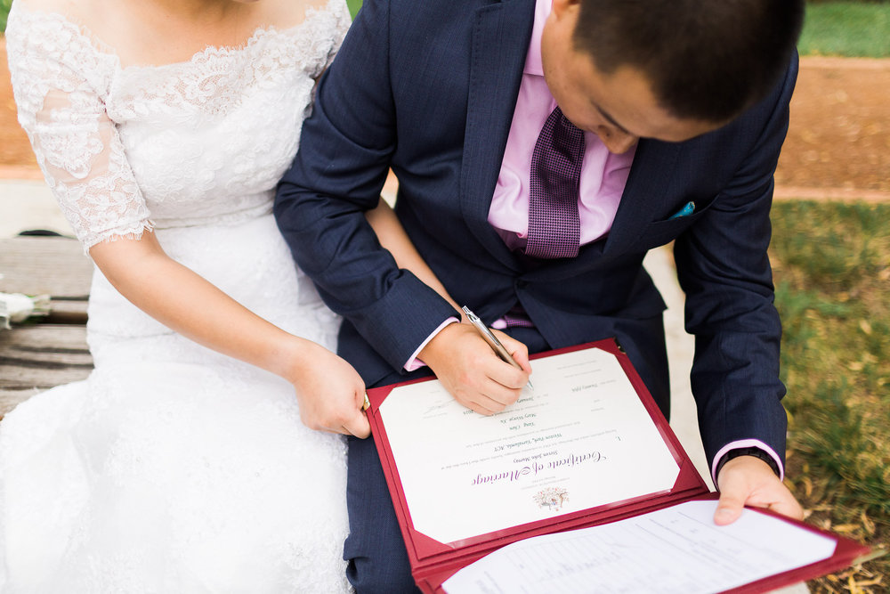 Couple signing the certificate at a Small Wedding in Weston Park, Canberra.
