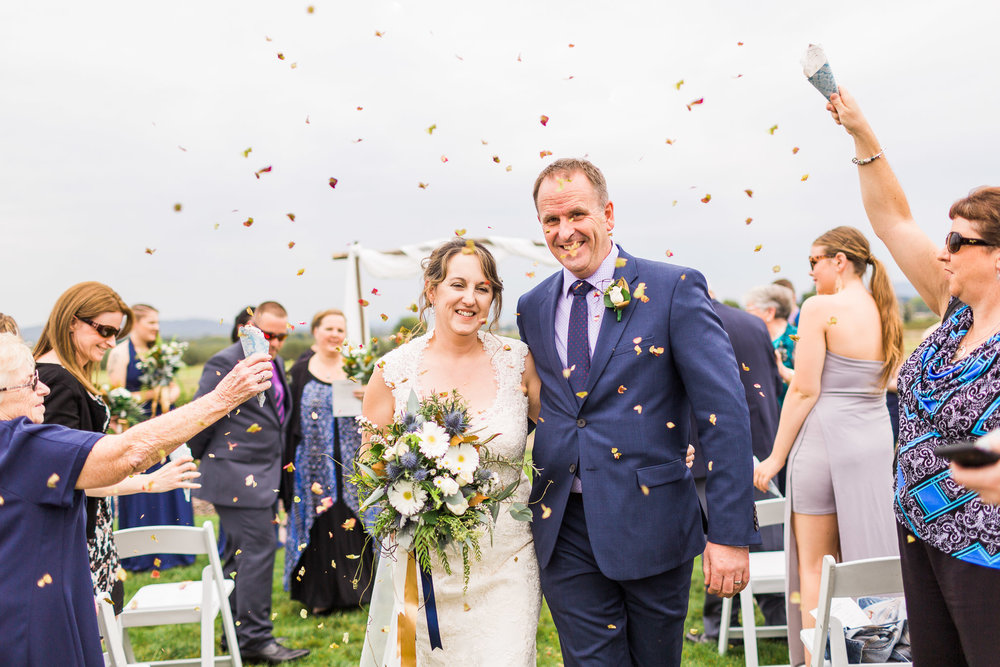 Guests throwing flower petal confetti at newly married couple - Pialligo Estate Wedding