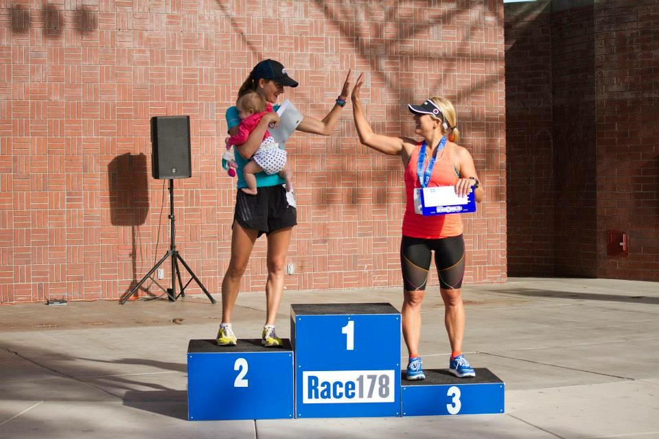 Here I am accepting my third-place award for the 10-mile run. Lauren Evans of eFast (who took 2nd in the run) is also my coach. I just love this picture. Photo Credit: Race178