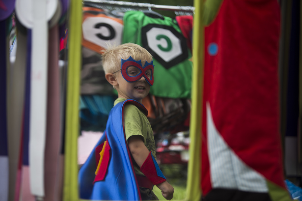 Carter Griesbaum, 4, of Irwin, looks in the mirror as he tries on superhero capes at the Arts and Heritage Festival at Twin Lakes Park in Greensburg, Pa. on Thursday, July 2, 2015.