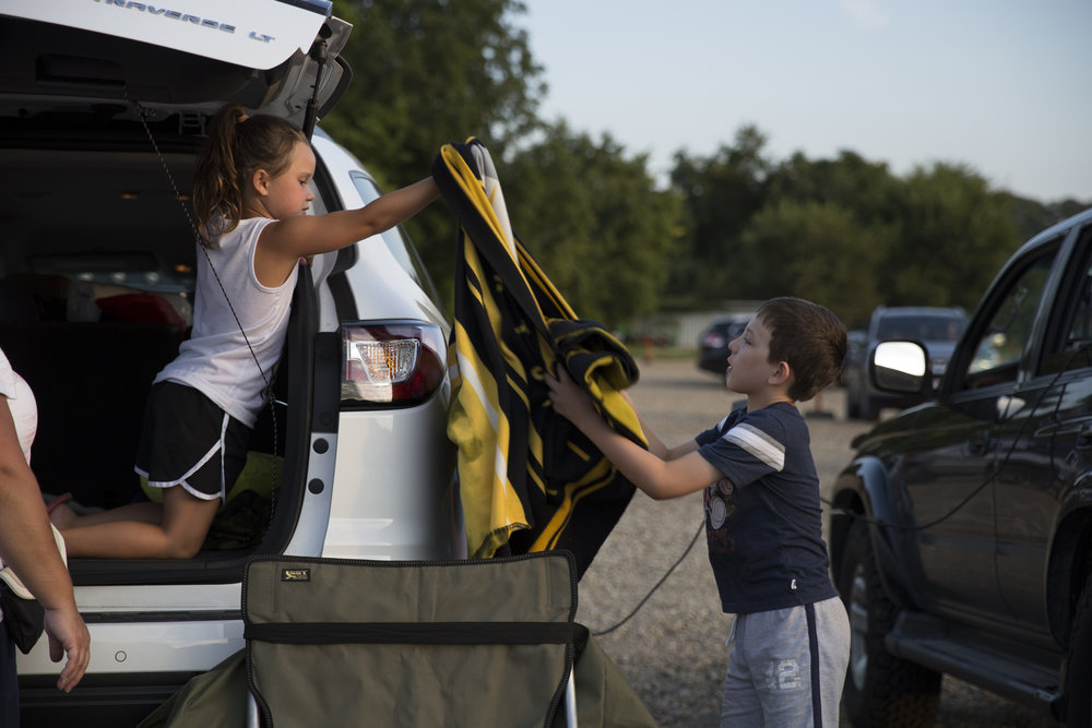 """Emma Kraynak, left, hands friend Evan Gardner a blanket while they prepare their family's vehicles for movie watching. Kraynak's father says the drive in is """"more of an adventure"""" than a normal movei theater and a great way to """"enjoy the end of the summer."""""""