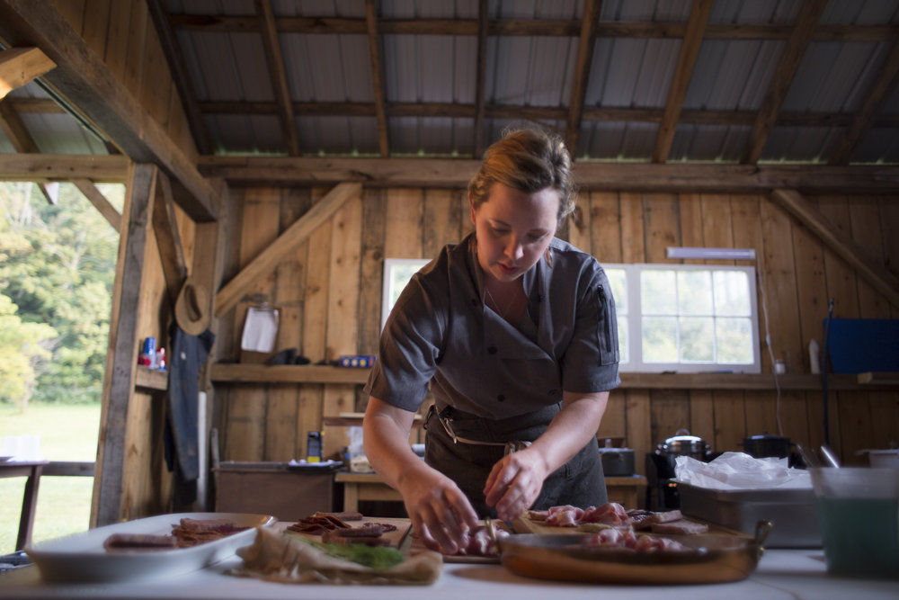 Becky Clark, chef-butcher and owner of Pork and Pickles, prepares a dish during a benefit dinner for Community Food Initiatives at Homecoming Farm in Amesville, Oh.