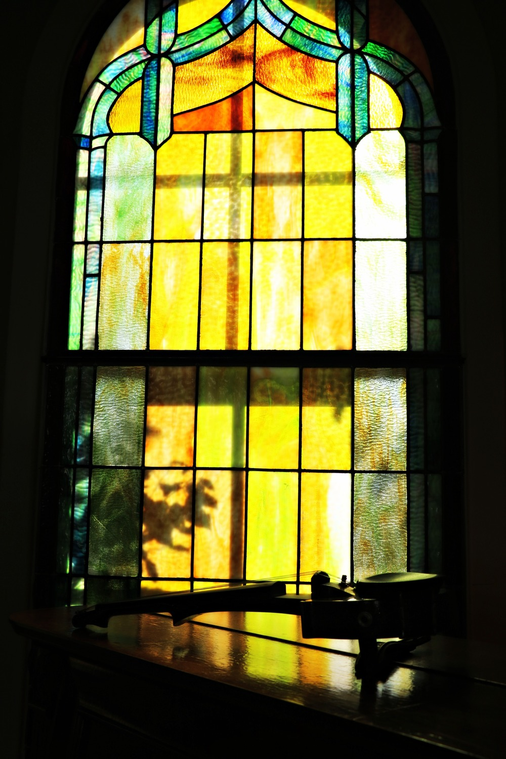 Silhouette of my violin in front of a stained glass window