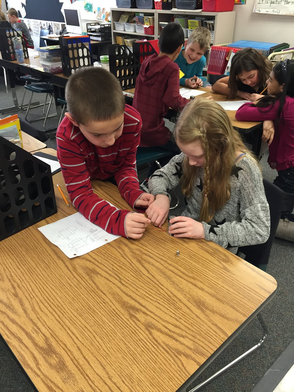 Students collaborate at an Inquiry Center - exploring the concept of Parts to Whole in science.