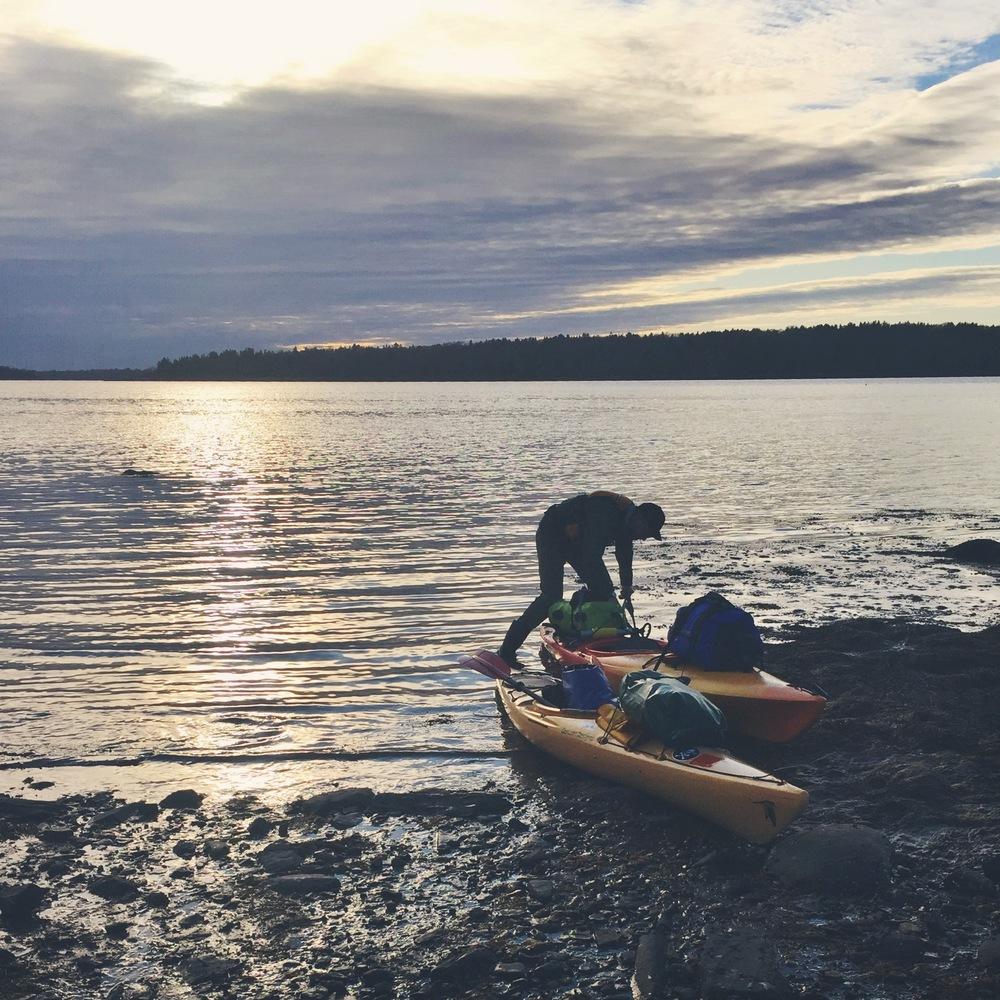 Teton unpacks his kayak while the sun sets behind him.