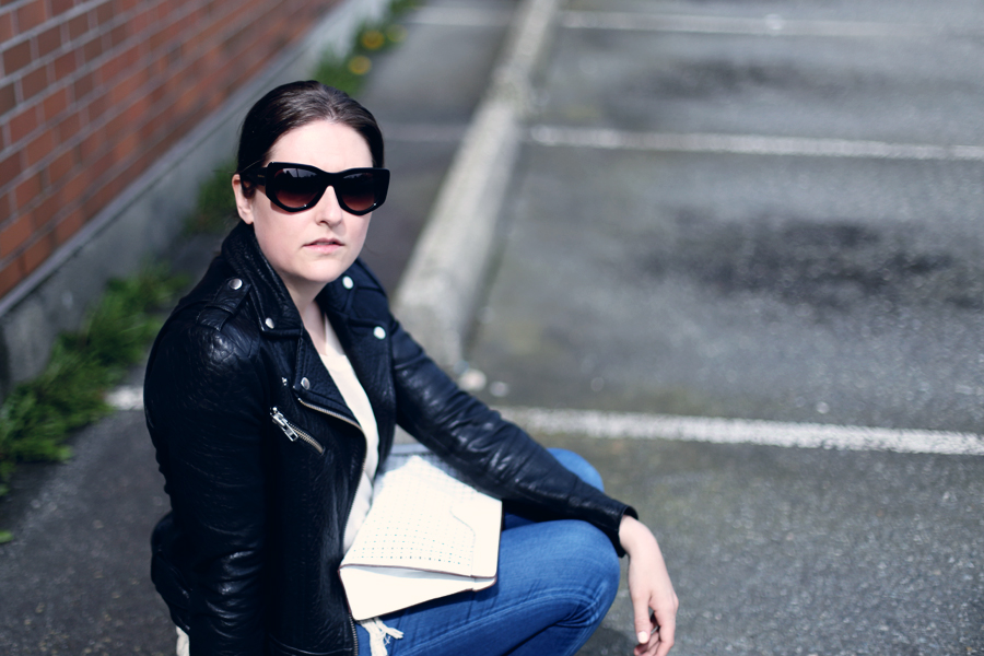 Minimalist street style: middle part hair, black leather jacket, and Balenciaga sunglasses.