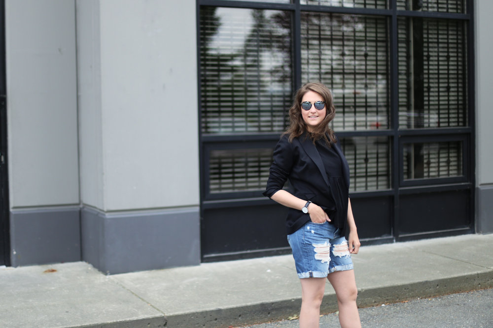 Minimalist fashion blog streetstyle: black blazer, black top, and ripped jean shorts.