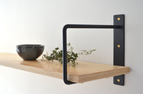 The best Etsy decor: black shelf brackets with gold screws and a pine shelf.
