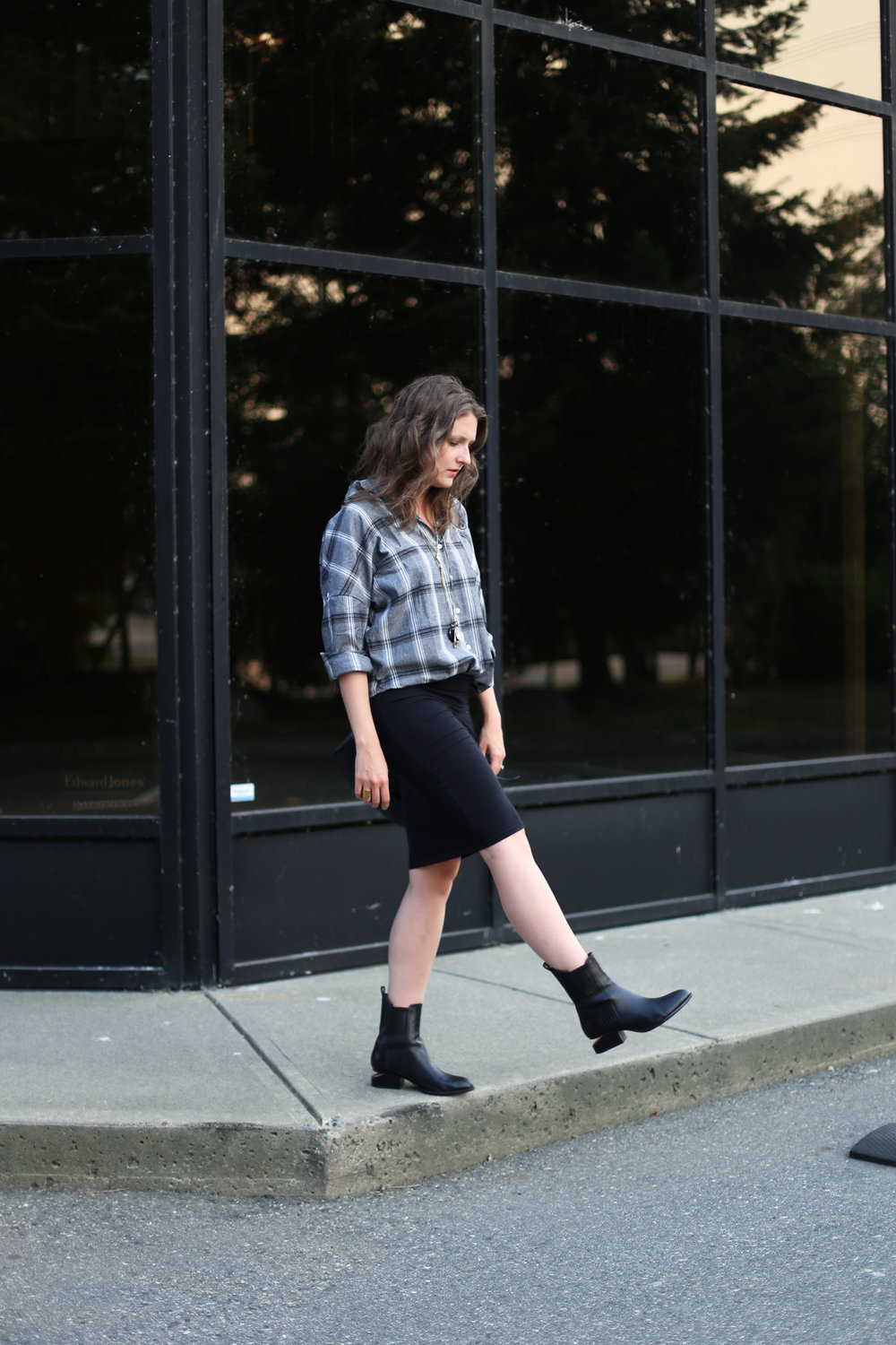 minimalist outfit ideas: black bag, black skirt, alexander wang boots, and a plaid shirt.