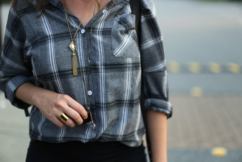 Minimalist outfit perfection: plaid shirt, layered gold necklaces, and a gold ring.