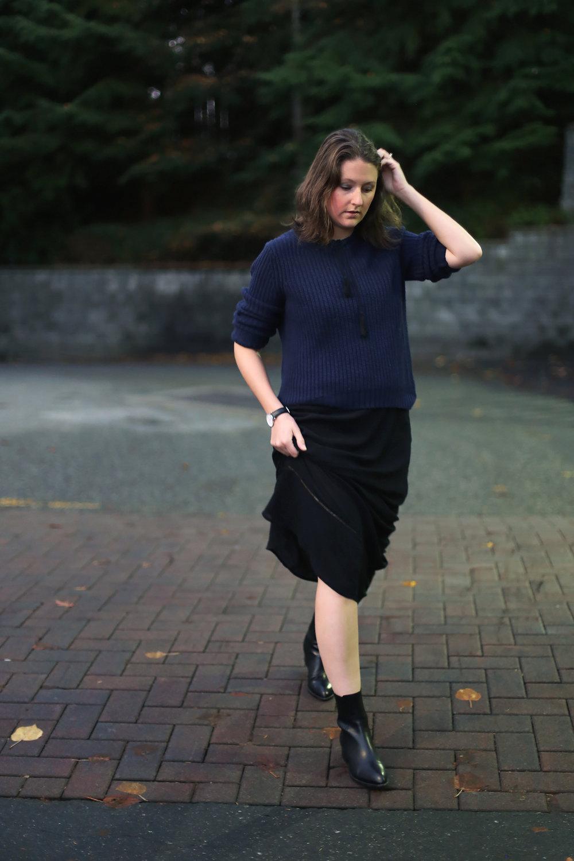 Minimalist street style: oversized sweater, black maxi dress, Alexander Wang boots, and a Daniel Wellington watch.