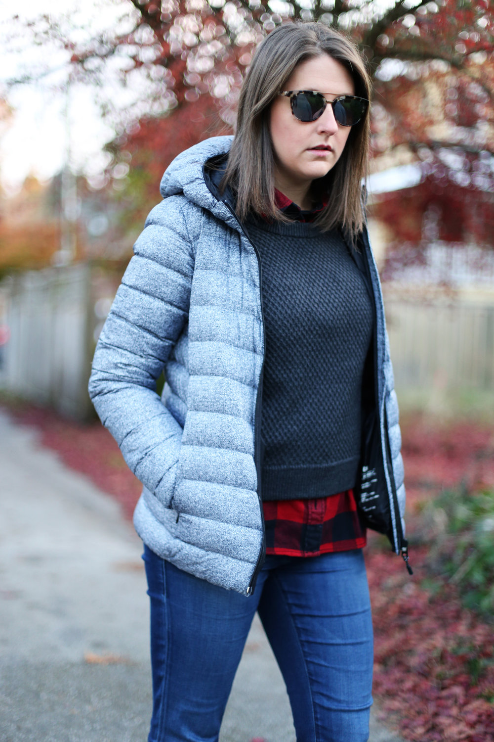 Winter minimalist street style: puffer coat, tortoise shell sunglasses, red and black plaid, and skinny jeans.