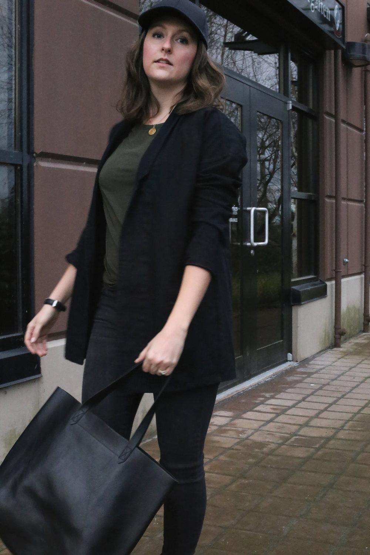 Black denim oversized blazer, black baseball hat, black jeans, and a black tote. Gorgeous street style.