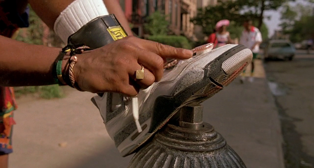 Do the Right Thing - A Spike Lee Join t  (1989).   The character cleans his shoes with a toothbrush after they have been scuffed.