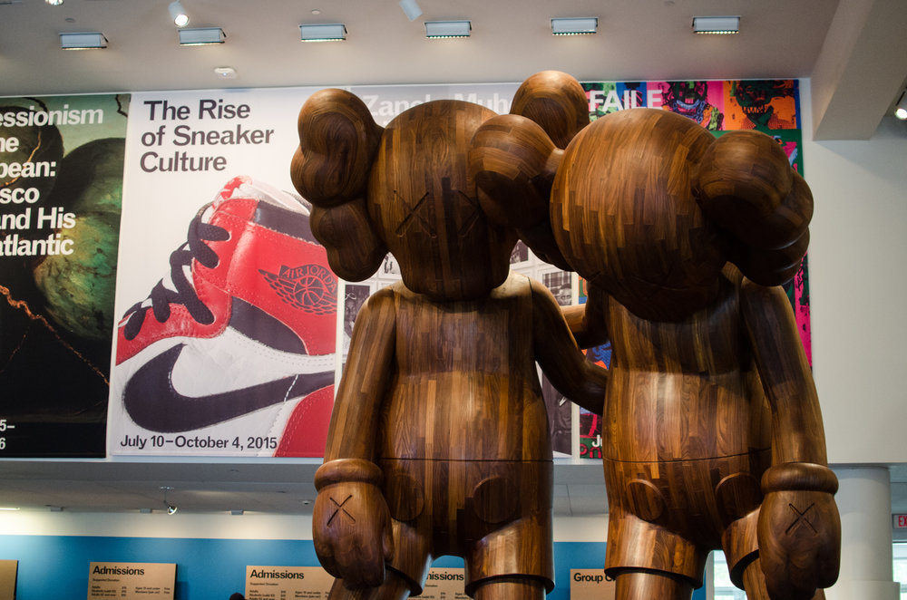 "Brooklyn Museum   with ""The Rise of Sneaker Culture""   sign next to two Kaws statues."