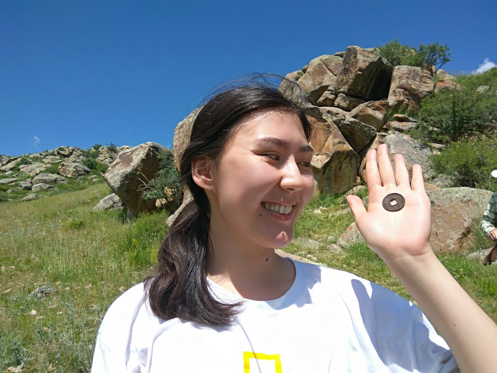 Student upon finding a Chinese coin issued around 570 CE. Coin was recovered from a Turkic period settlement excavated by the DMAP in 2017.