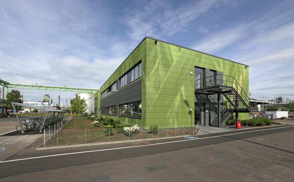Fassadengestaltung-Industrie-Betriebszentrale-fassadenbau-Buerogebaeude-Bayer-Eternit-wiese-motiv-umwelt.jpg