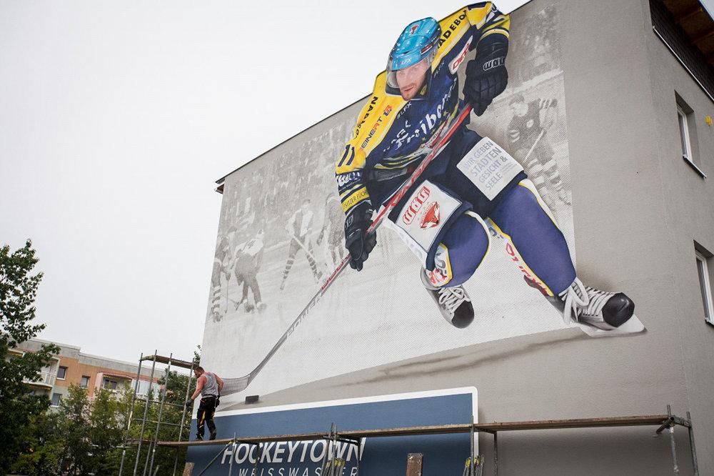 Fassaden-Gestaltung-Wohnungsbau-plattenbau-Wandbild-Eishockeyspieler-Weißwasser-Werbung.jpg