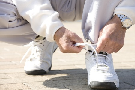 47076551_S_man_senior_exercise_sneakers_watch_tie_laces_bend.jpg