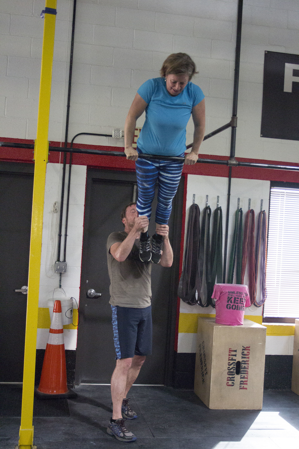 Jill and Peter, assisting in a bar muscle up.