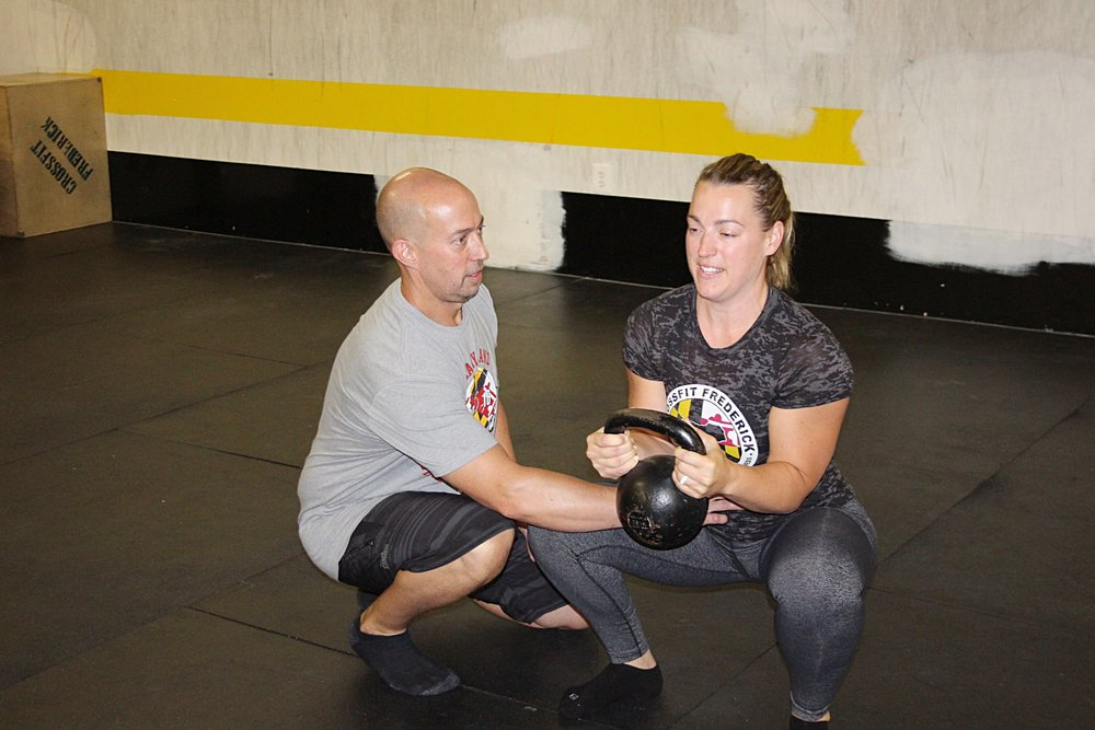Megan demonstrating the goblet squat that is in today's WOD.
