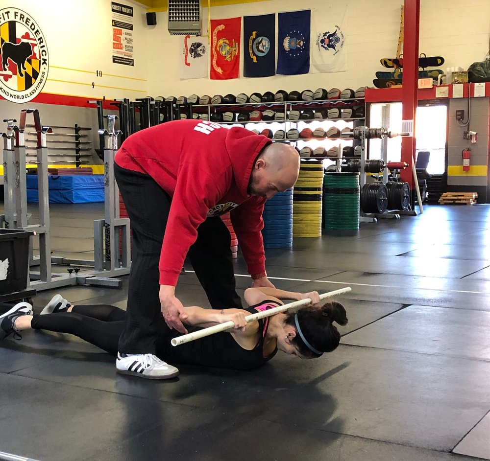 Coach Dave assisting Priscila with the prone behind the neck press to ensure proper mechanics.